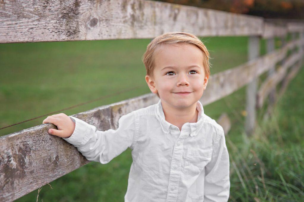 blonde preschool boy standing next to wooden fence at golden hour