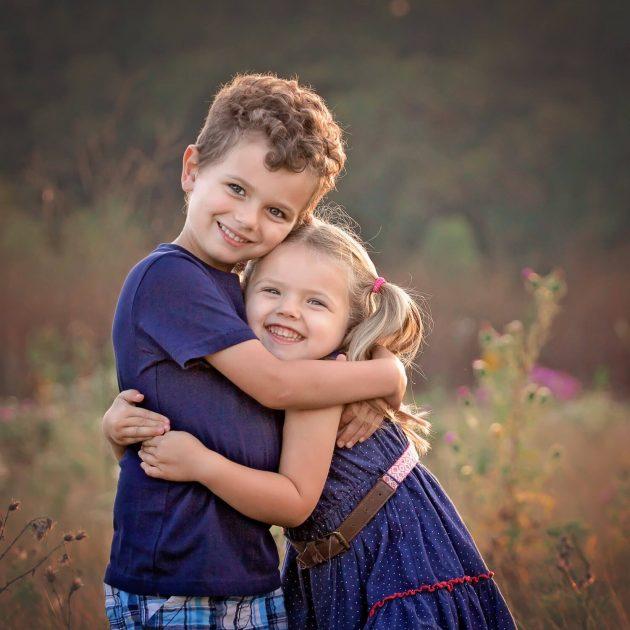 boy girl siblings hugging in a tall grass field