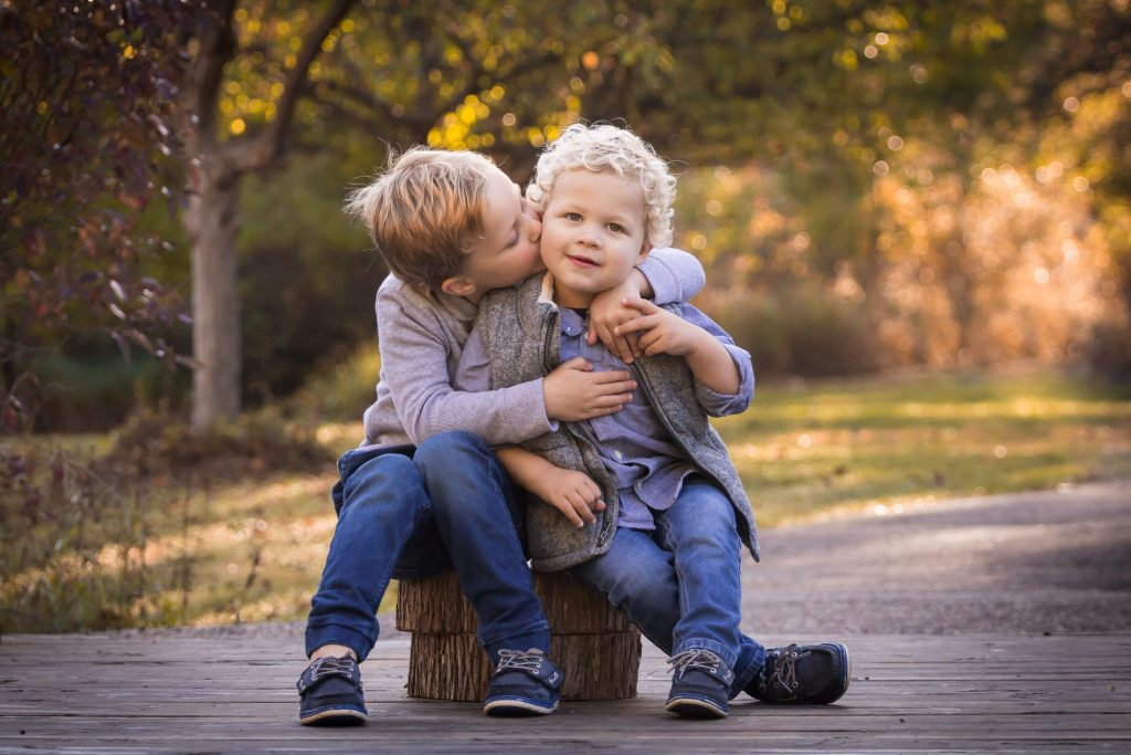 boy kissing younger brother's cheek sitting on tree stumps