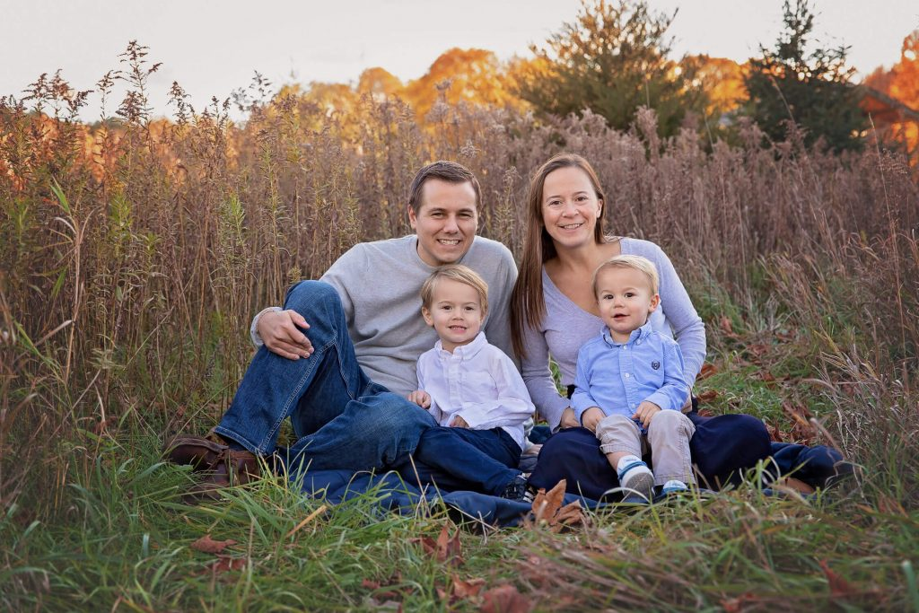 Family of four sitting on a blanket in a tall grass field at sunset