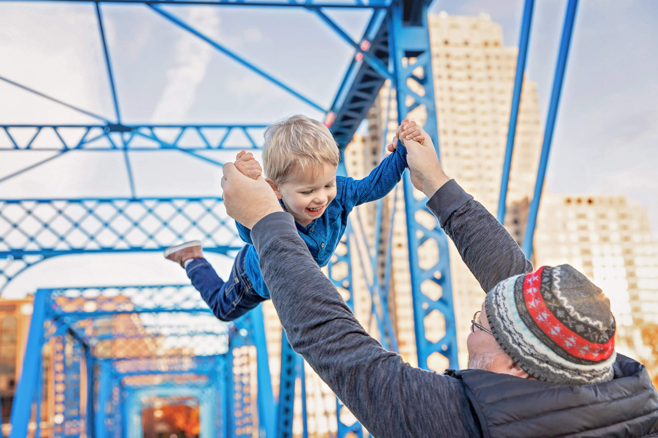 dad lifting toddler son in air on the Blue Bridge
