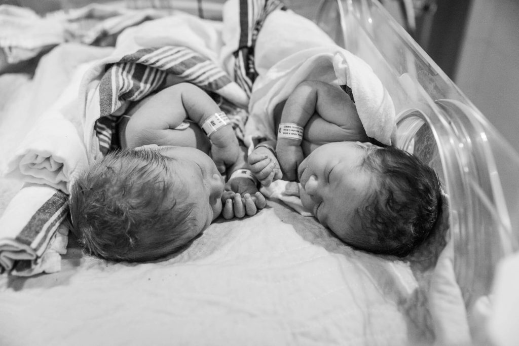 black and white boy and girl twins snuggled in hospital isolette