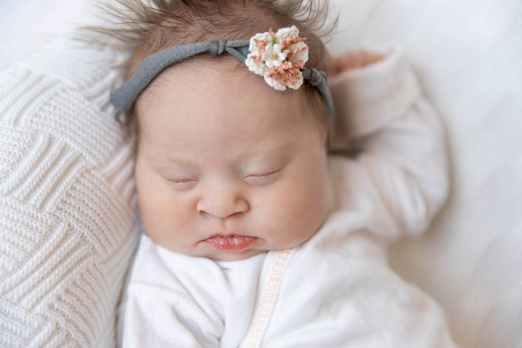 newborn girl wearing gray and pink headband sleeping on white blanket