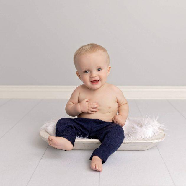 9 month old boy sitting in white trough wearing navy pants smiling at camera