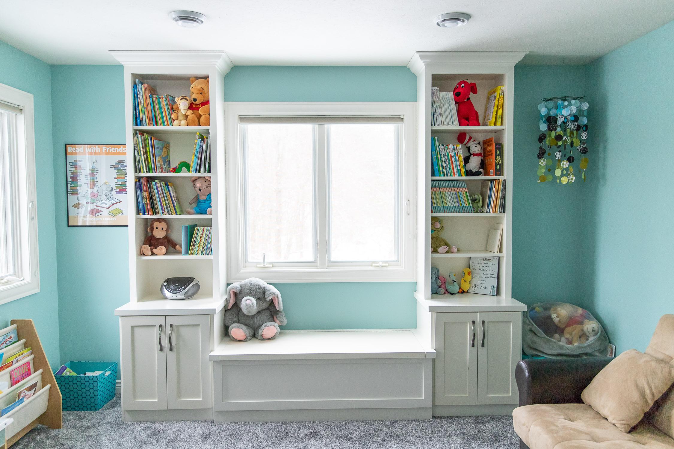 White built in bookshelves full of children's books in a turquoise room