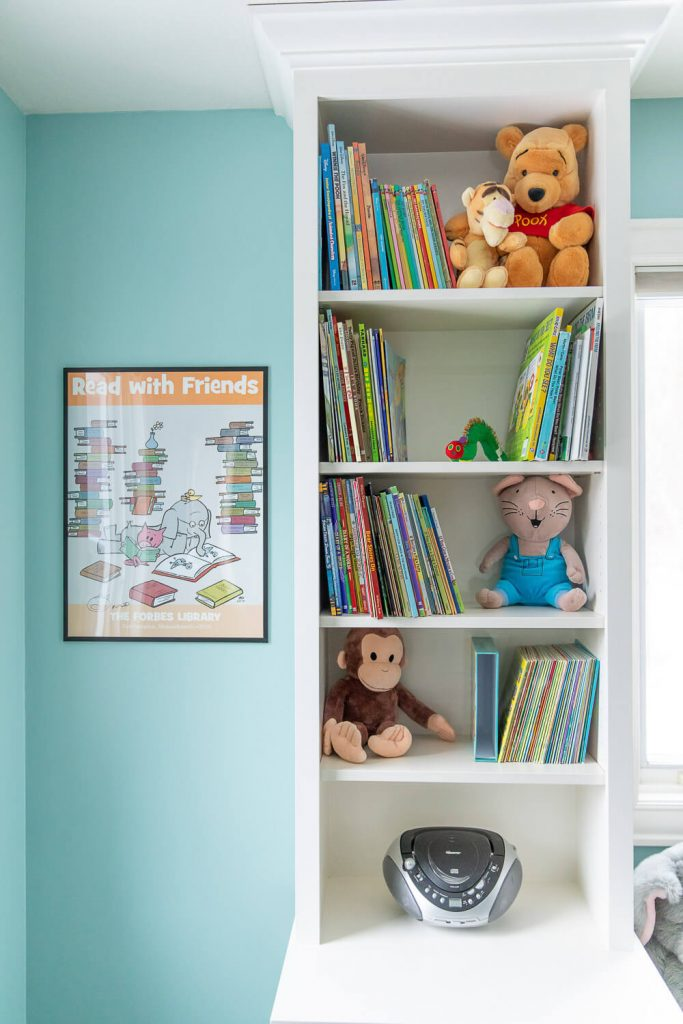 """Bookshelf with a Mo Willems poster that says """"Read With Friends"""""""