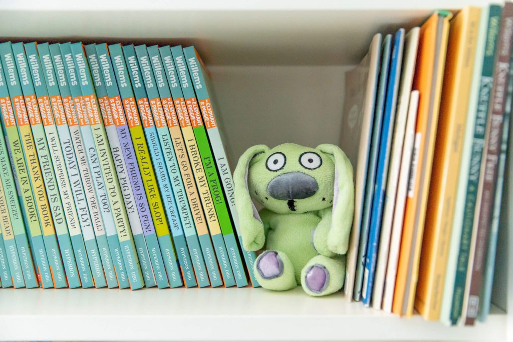 Close up of bookshelf showing Mo Willems books and a stuffed Knuffle Bunny