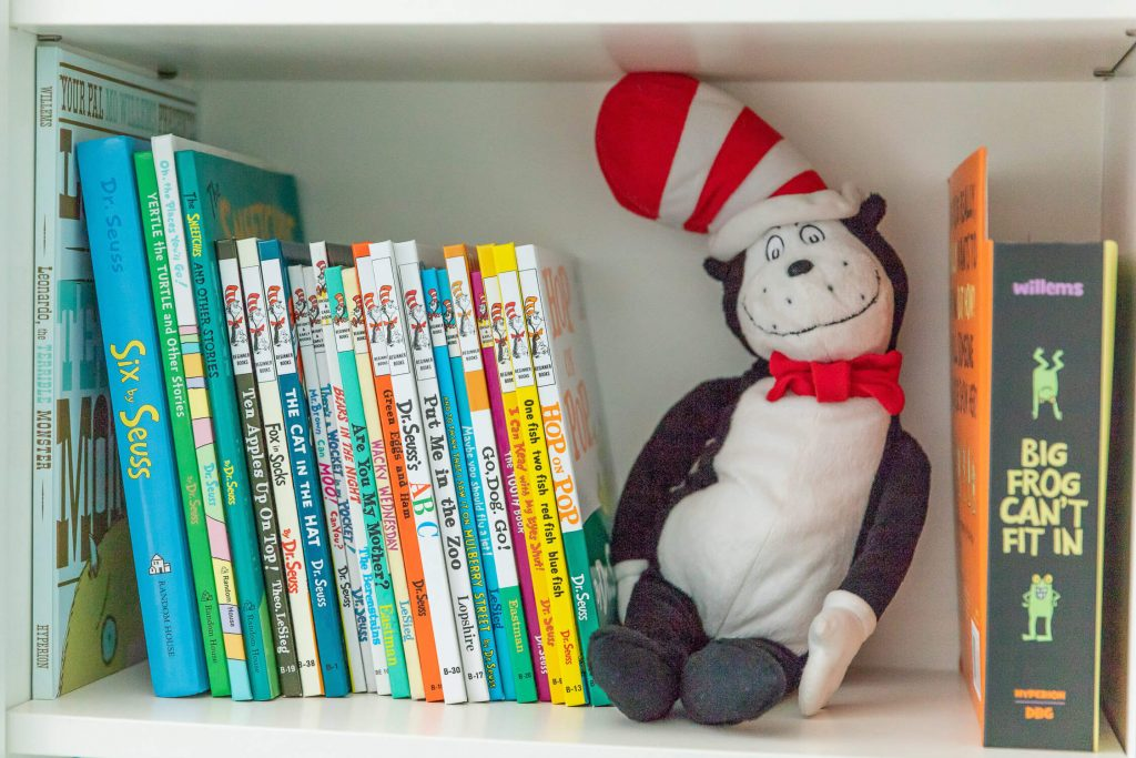 Closeup of bookshelf showing Dr. Seuss books and a Cat in the Hat stuffed animal