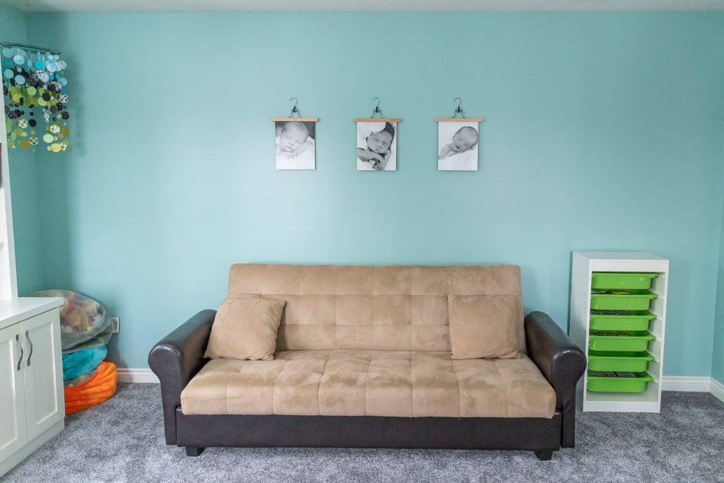 futon in bookroom with three newborn photos hanging above it