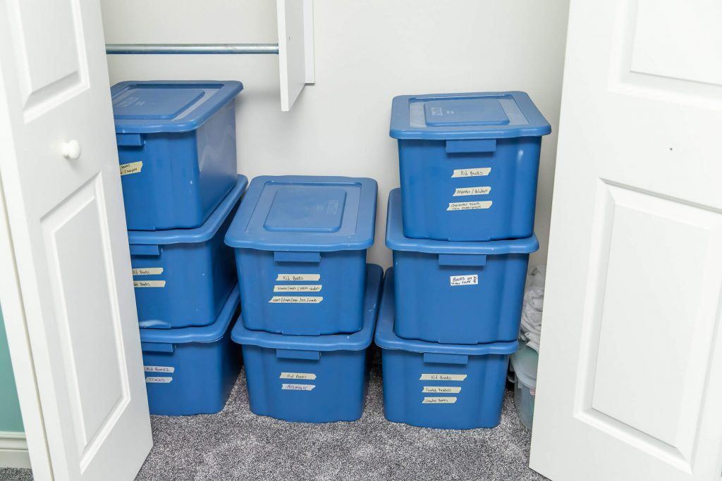 Opened closet with 8 blue tubs of books