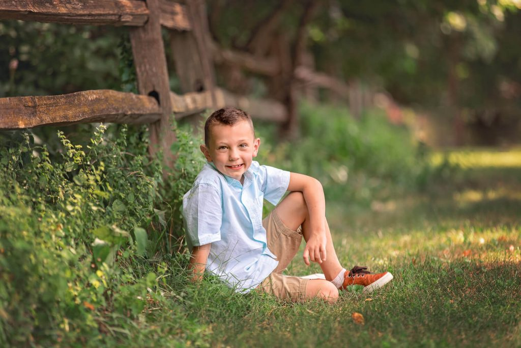 young boy sitting leaned against a wooden fence in a tall grass field