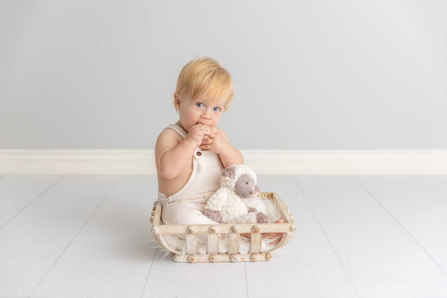 baby boy wearing white overalls sitting in a white bowl with lamb in a white studio
