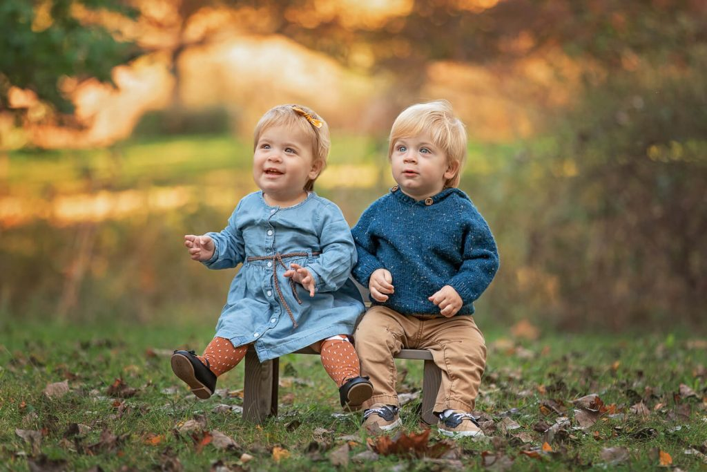 twin 1 year old siblings sitting on a bench under autumn trees
