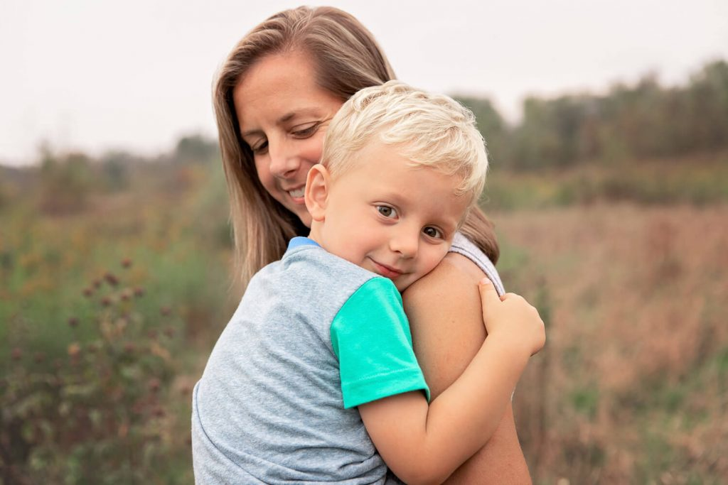 Mom holding and smiling at toddler son while he rests his head on her shoulder looking at camera