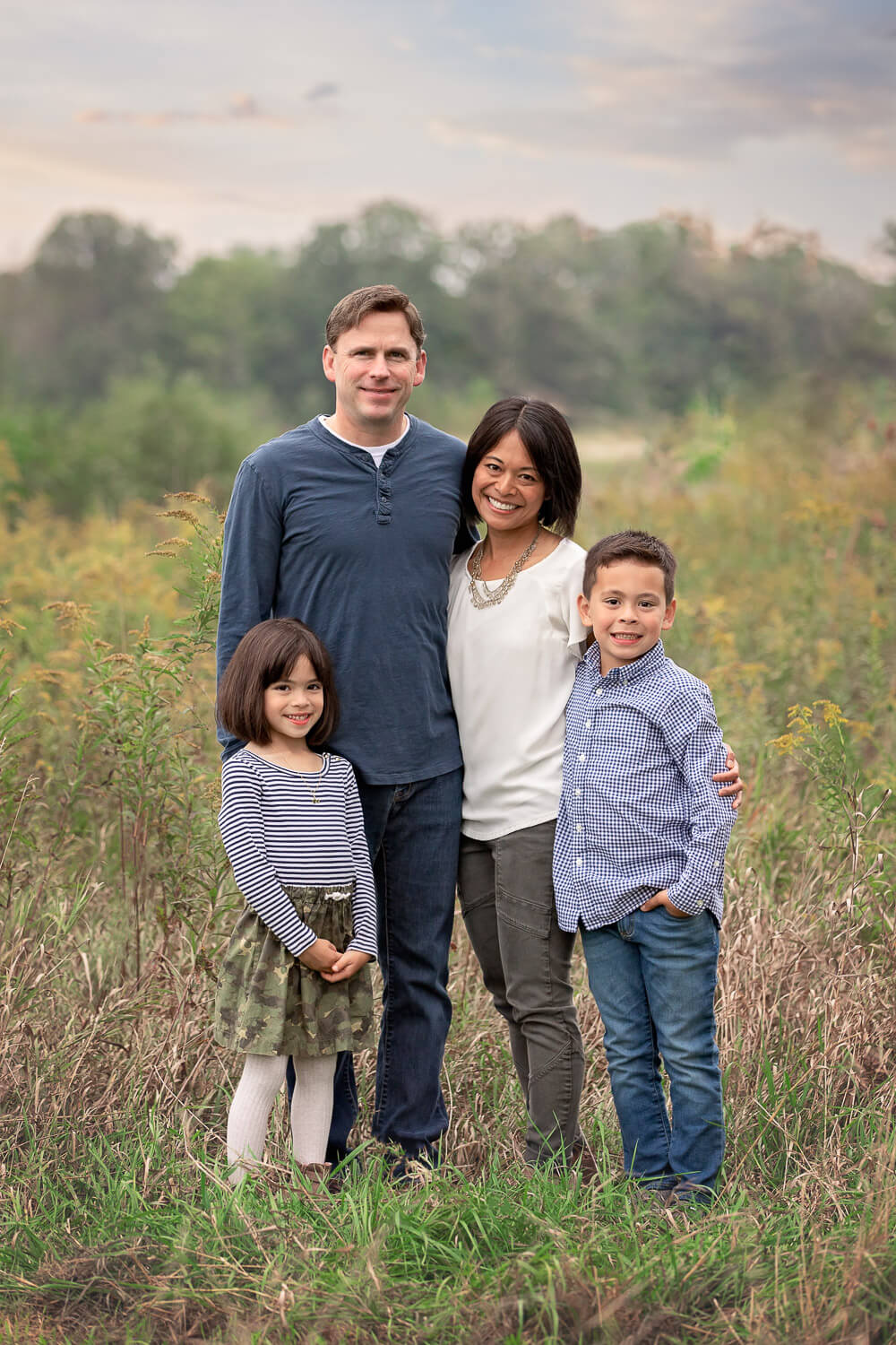 Family of 4 standing in a tall grass field