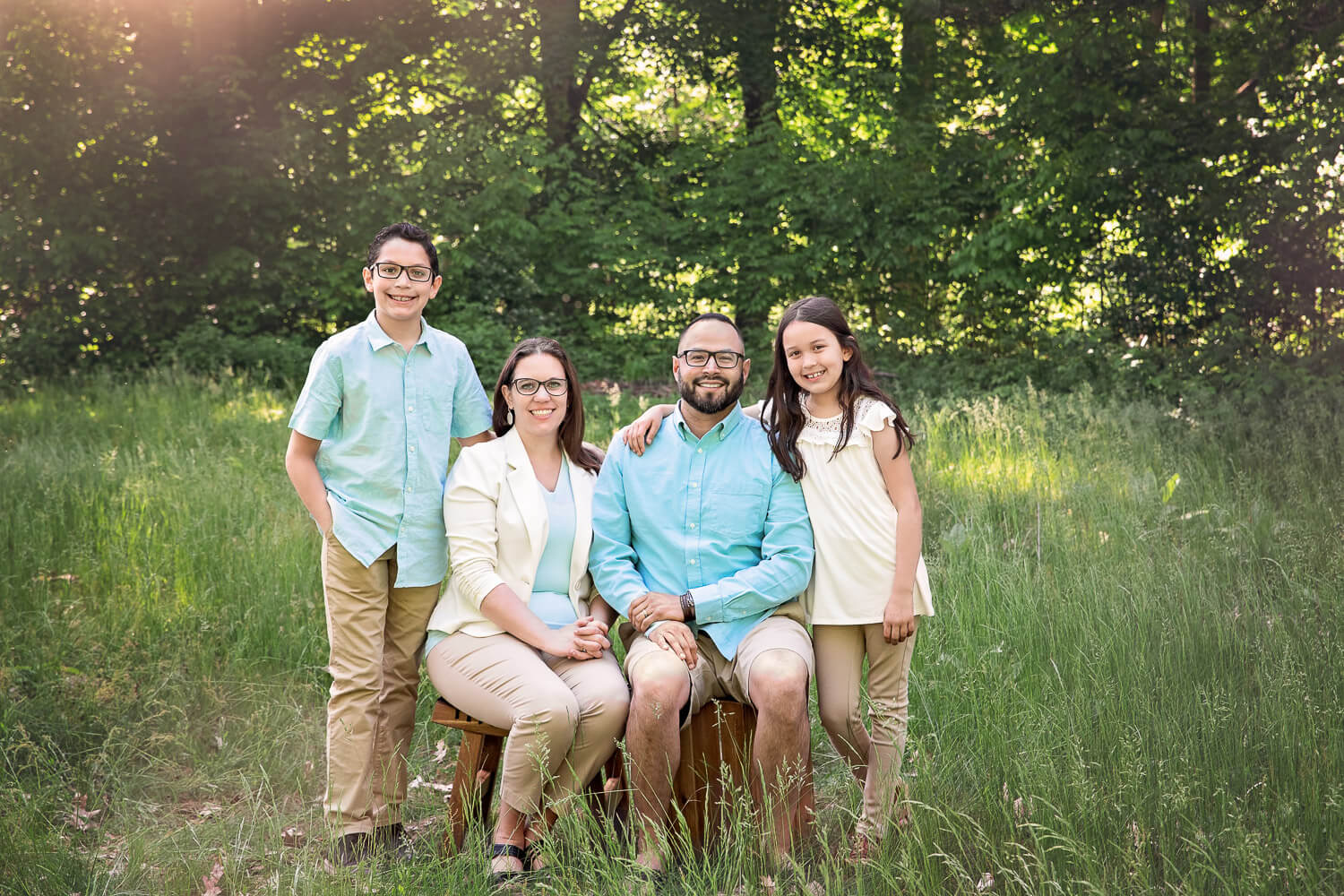 Family of 4 portrait surrounded by tall grasses and trees with sun rays shining on them