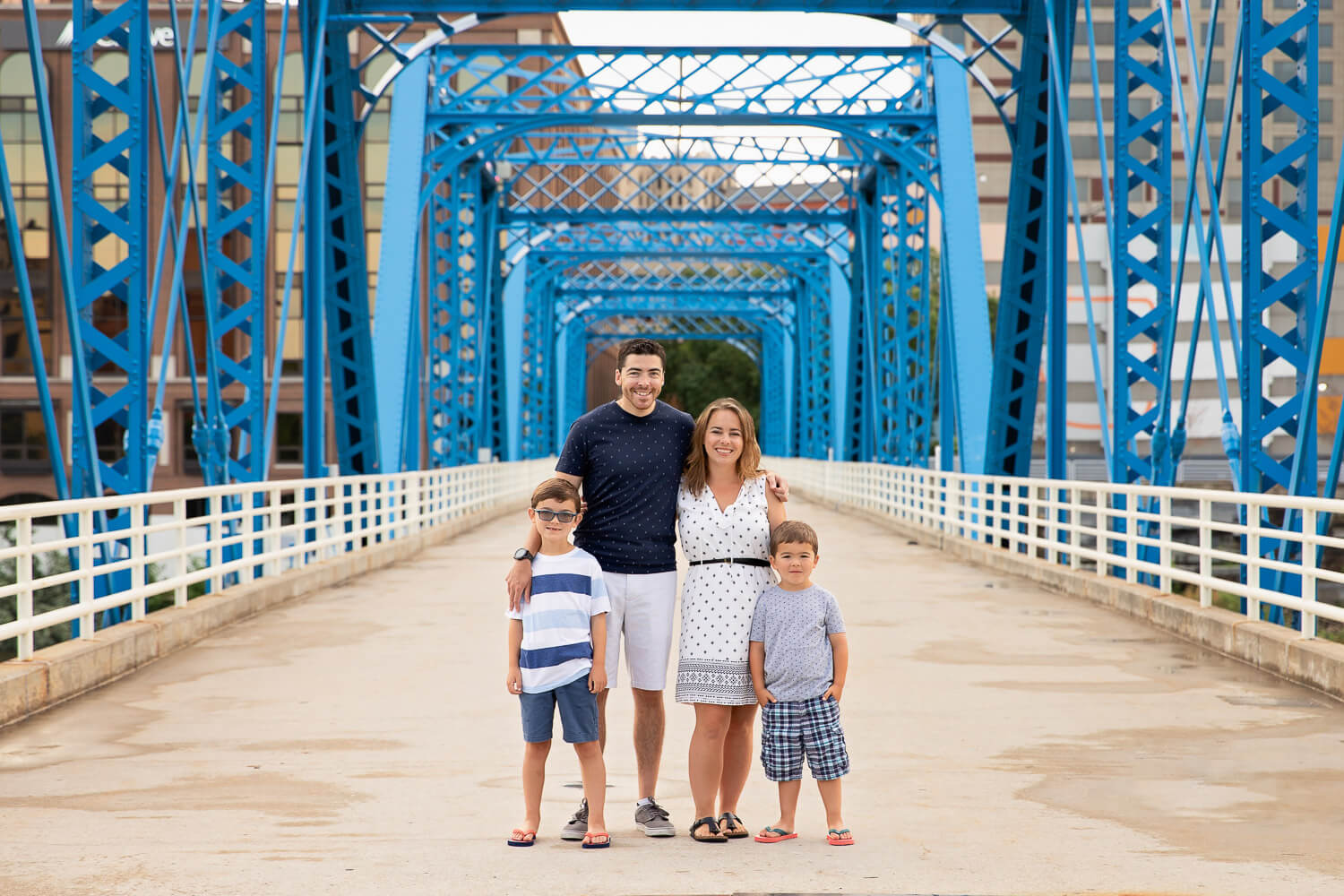 Family of 4 standing on the Blue Bridge in Grand Rapids