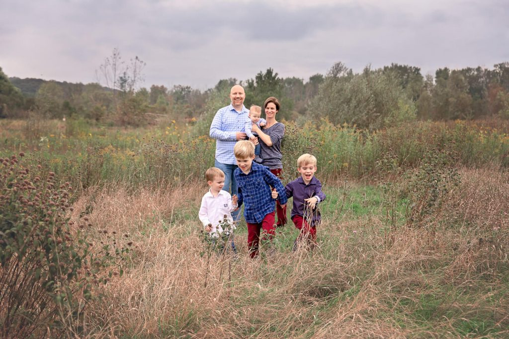 3 young brothers running towards camera while mom, dad and brother stand in the background of a tall grass field