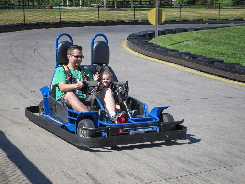 a dad and his toddler daughter riding go carts at Craig's Cruisers
