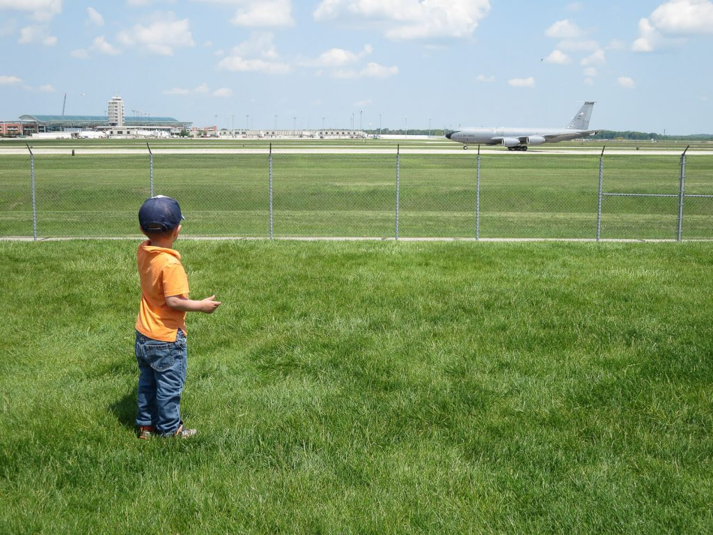 toddler boy waving at airplane at GRR Ford Airport