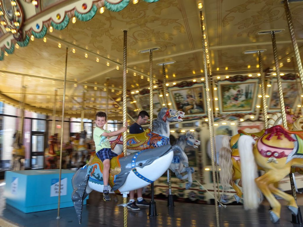 young boy spinning on a carousel at the Grand Rapids Public Museum