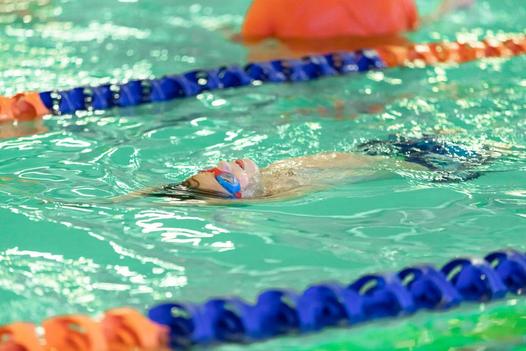 young boy with blue goggles swimming on his back at Goldfish Swim School