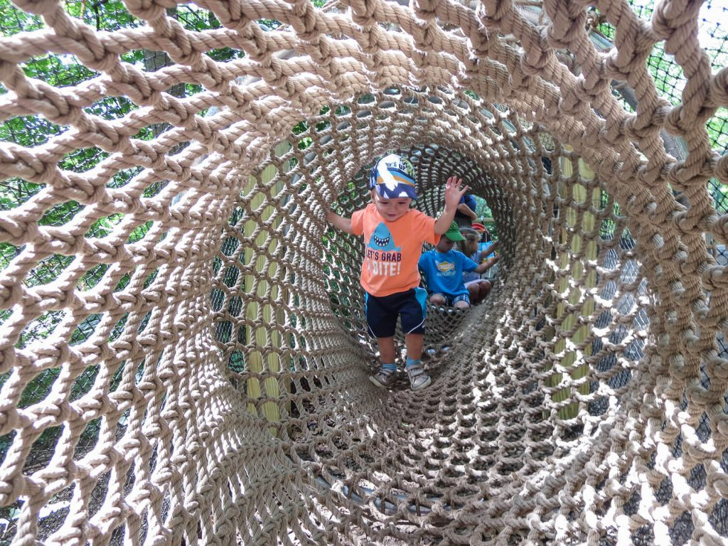 toddler boy walking through a rope tunnel at John Ball Zoo