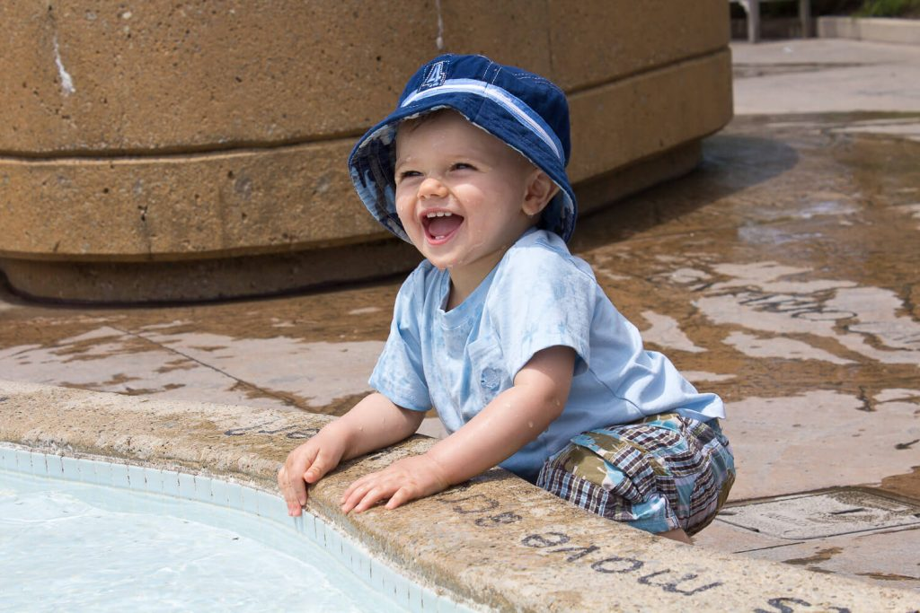 baby boy wearing a blue fishing hat smiling and splashing in water at Meijer Gardens