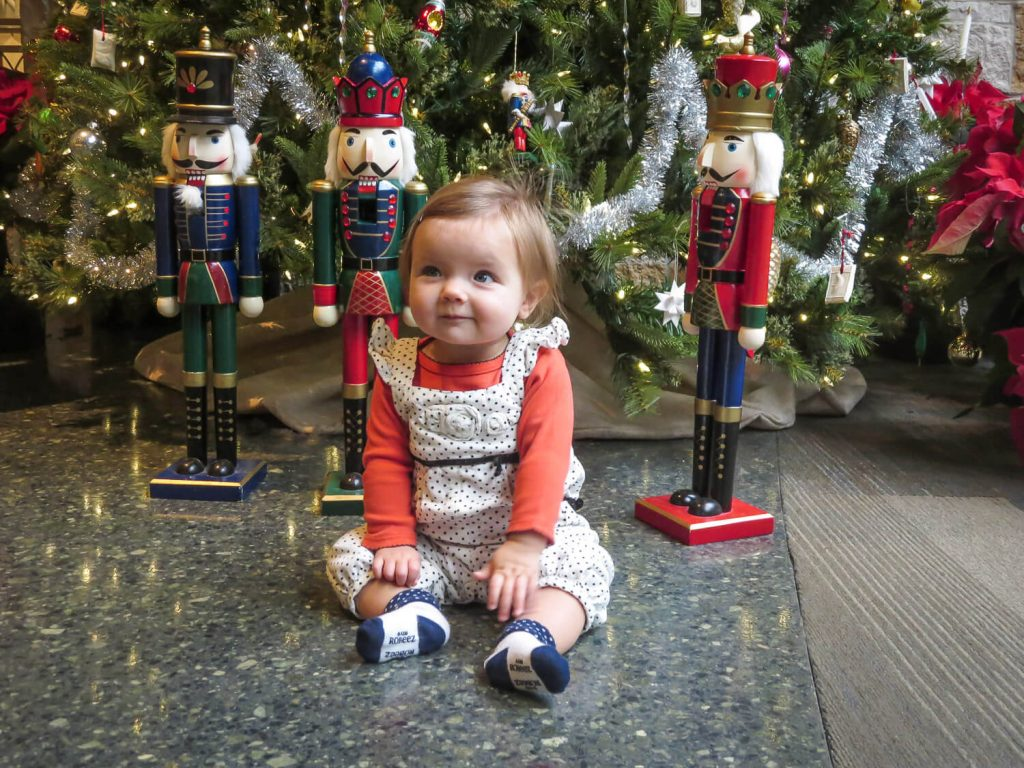 baby girl sitting on the floor in front of nutcrackers and Christmas trees at Meijer Gardens