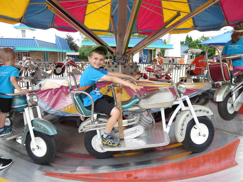 young boy sitting on a spinning motorcycle ride at Michigan's Adventure