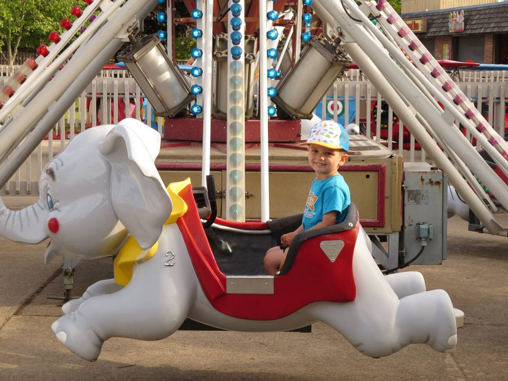 toddler boy sitting in an elephant ride at Michigan's Adventure