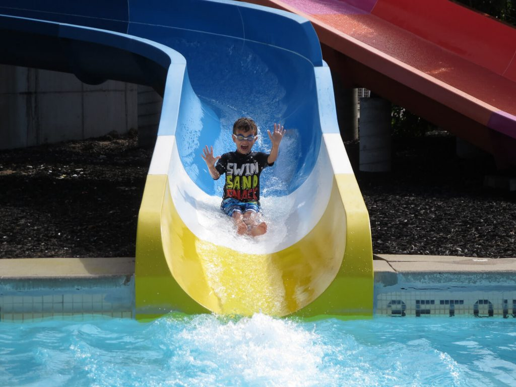 young boy wearing goggles sliding down a water slide at Michigan's Adventure