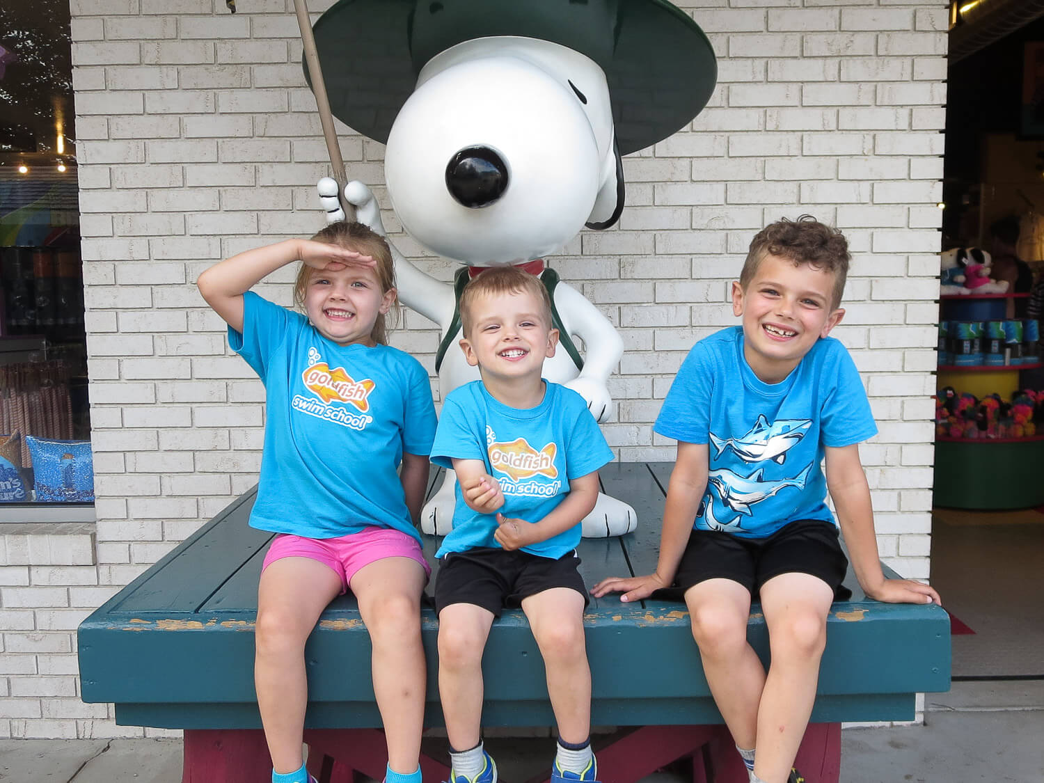 three young siblings sitting on a platform with a Snoopy statue at Michigan's Adventure