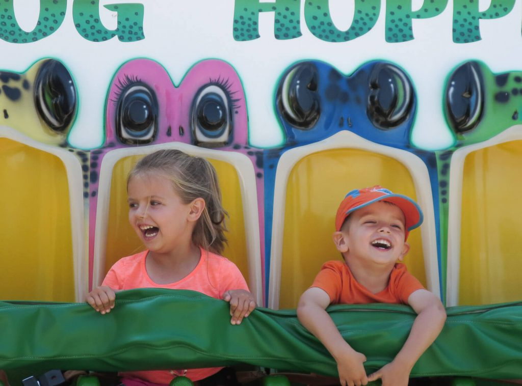 young girl and boy laughing on Frog Hopper ride at Michigan's Adventure