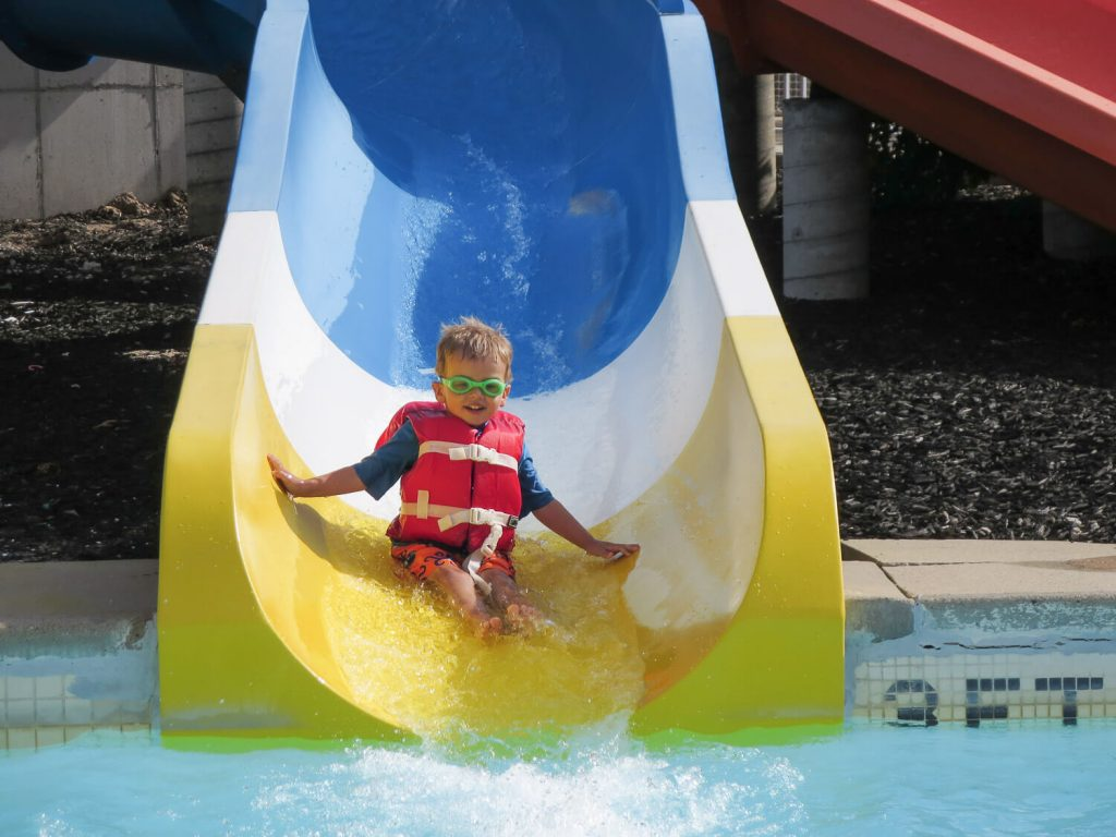 toddler boy wearing a life jacket and goggles sliding down a water slide at Michigan's Adventure