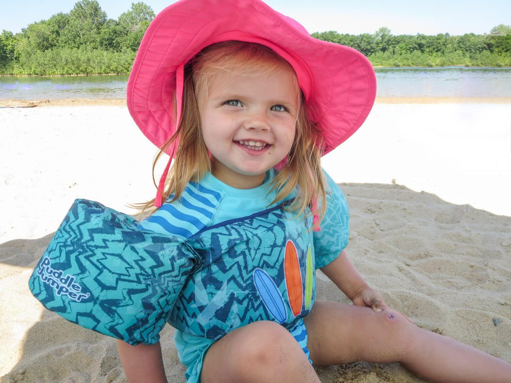 toddler girl wearing a pink sun hat sitting in the sand at Millennium Park in Grand Rapids