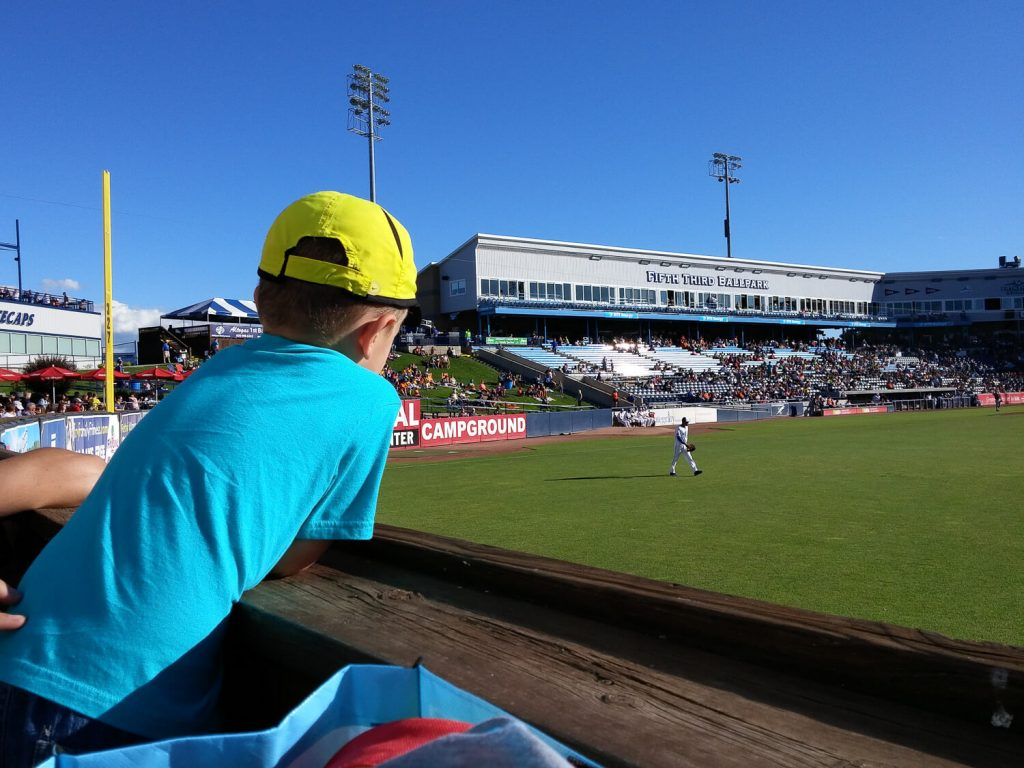 young boy leaning over the wall overlooking right field watching the Whitecaps at Fifth Third Ballpark