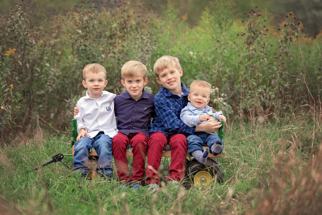 4 young brothers sitting in a wagon in a tall grass field