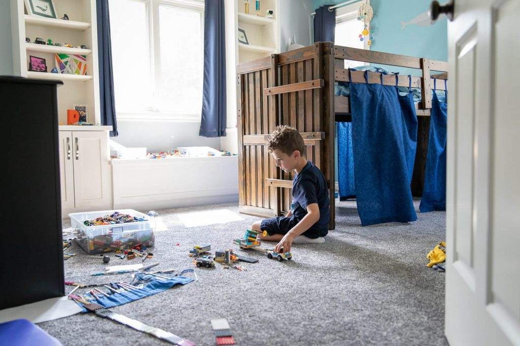 wide angle view of young boy playing with Legos on his bedroom floor