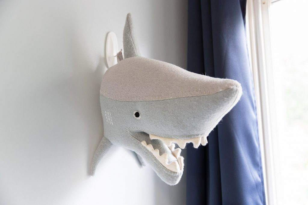 close up of felt shark head hanging on bedroom wall