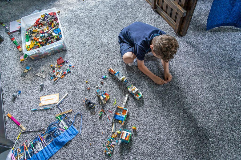 birdseye view of young boy playing Legos on his bedroom floor