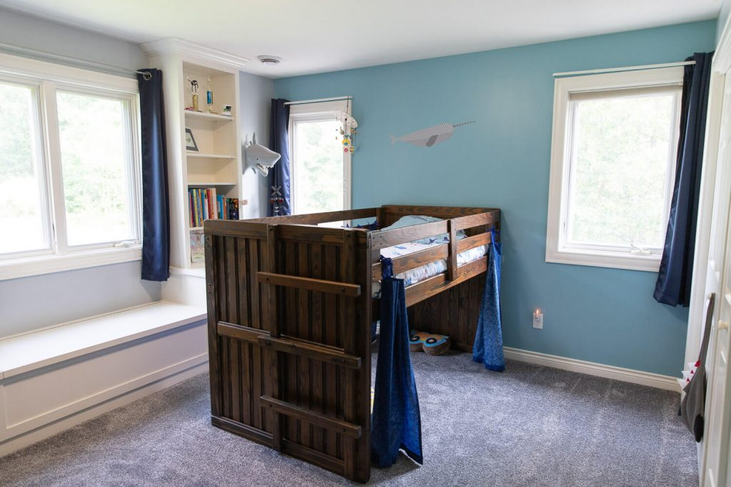 wide angle view of boys bedroom with wood loft bed and blue accent wall