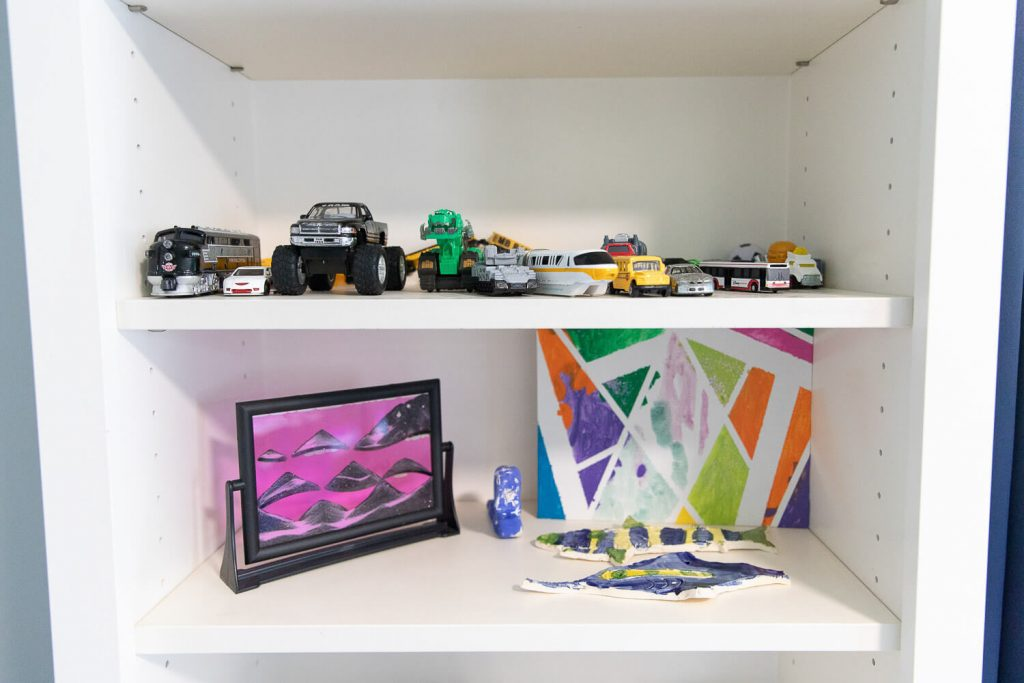 close up of art projects and truck toys on built in shelves