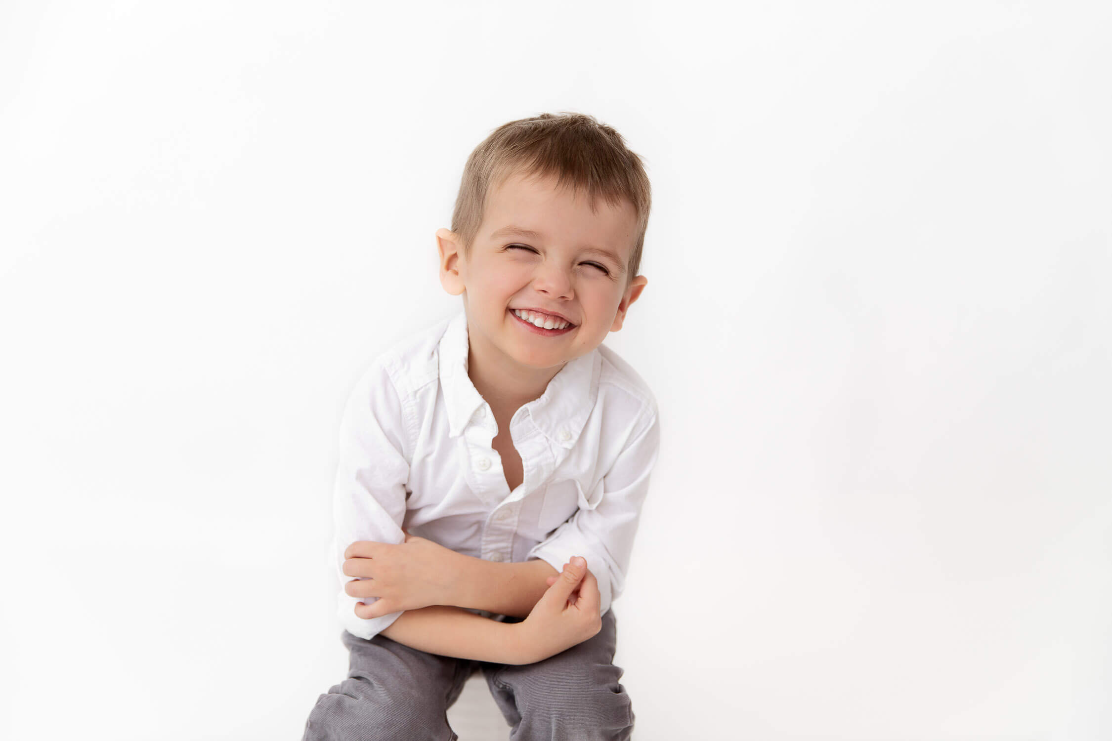 young boy with big squinty smile at camera with arms crossed
