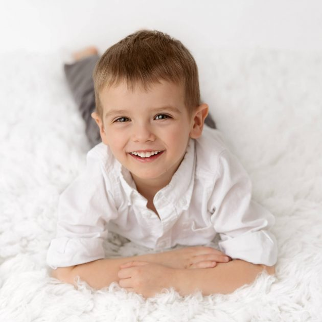 young boy laying on stomach on white fur smiling up at camera