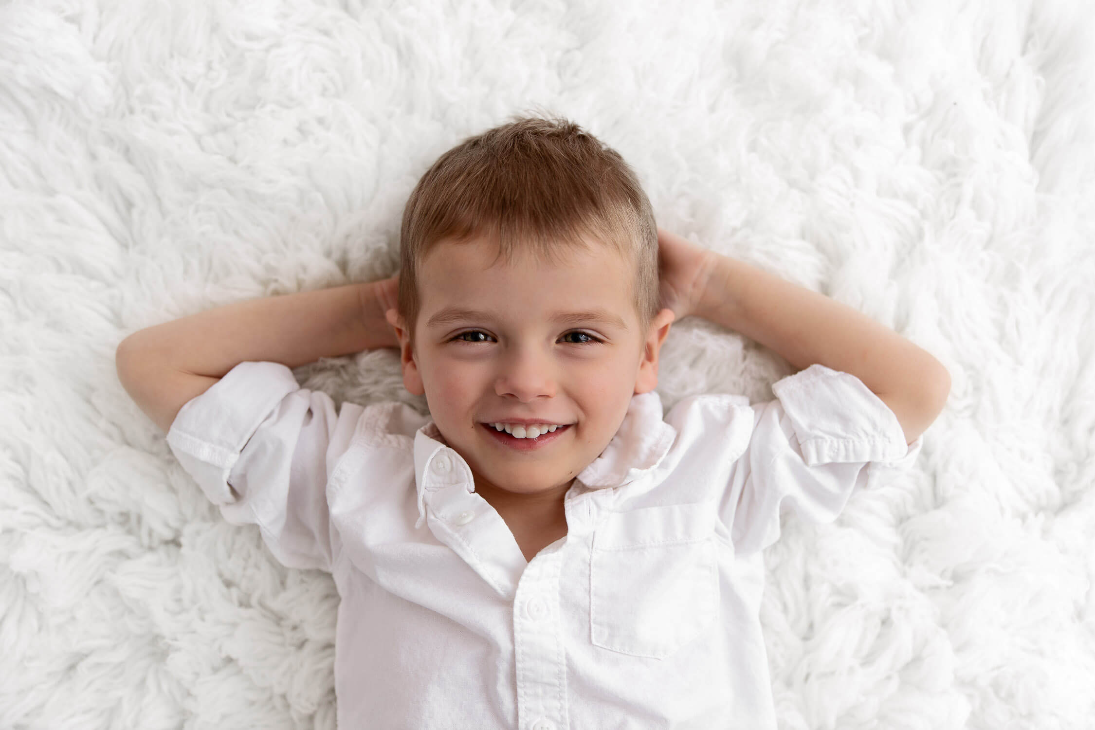 4 year old boy laying on white fur with hands behind head smiling up at camera
