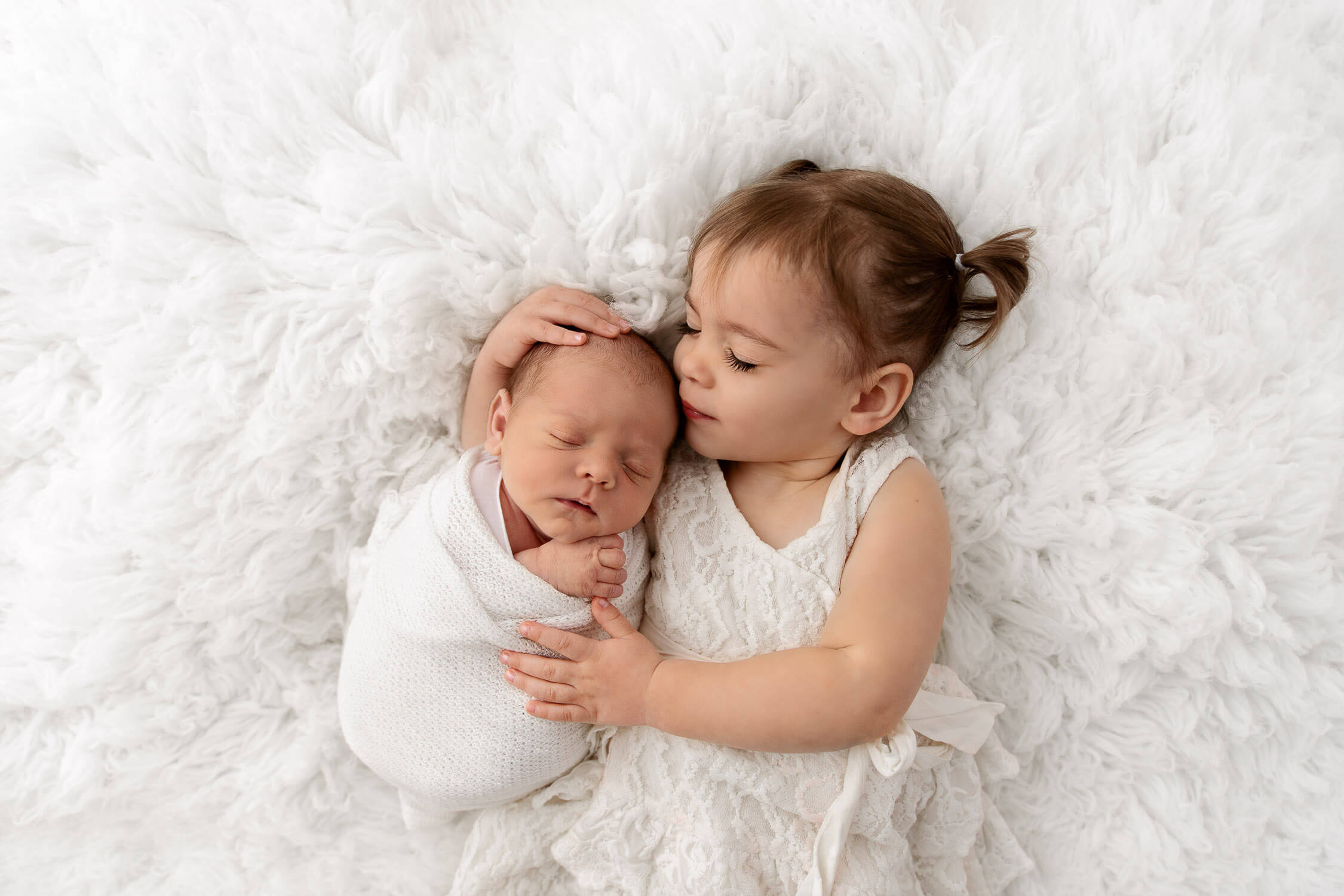 toddler sister with eyes closed holding sleeping baby brother on white fur