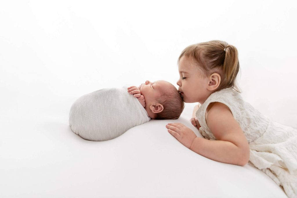 backlit toddler sister kissing the head of baby brother wrapped in a white wrap on white beanbag