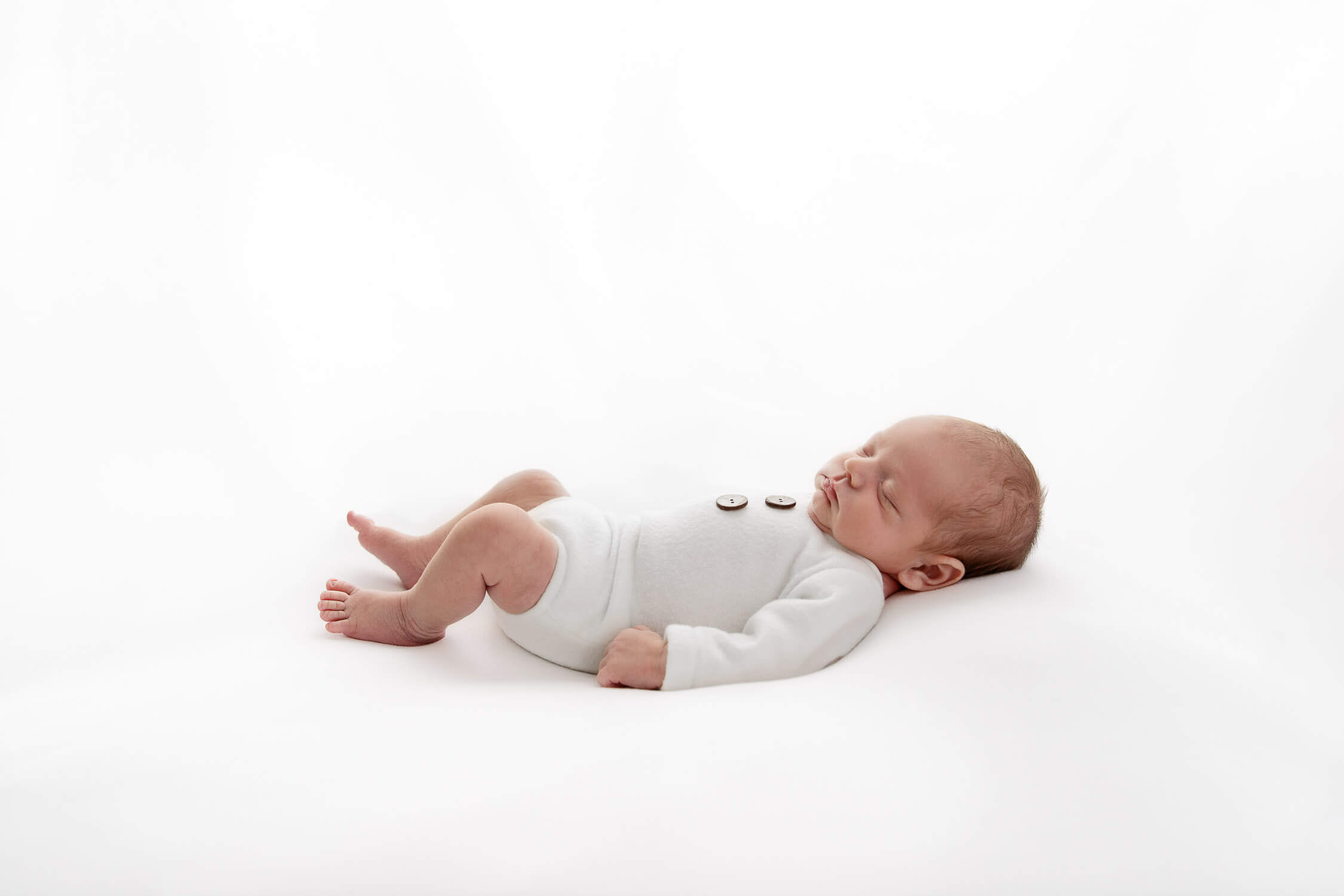 backlit newborn baby boy wearing white romper laying on his back on white beanbag