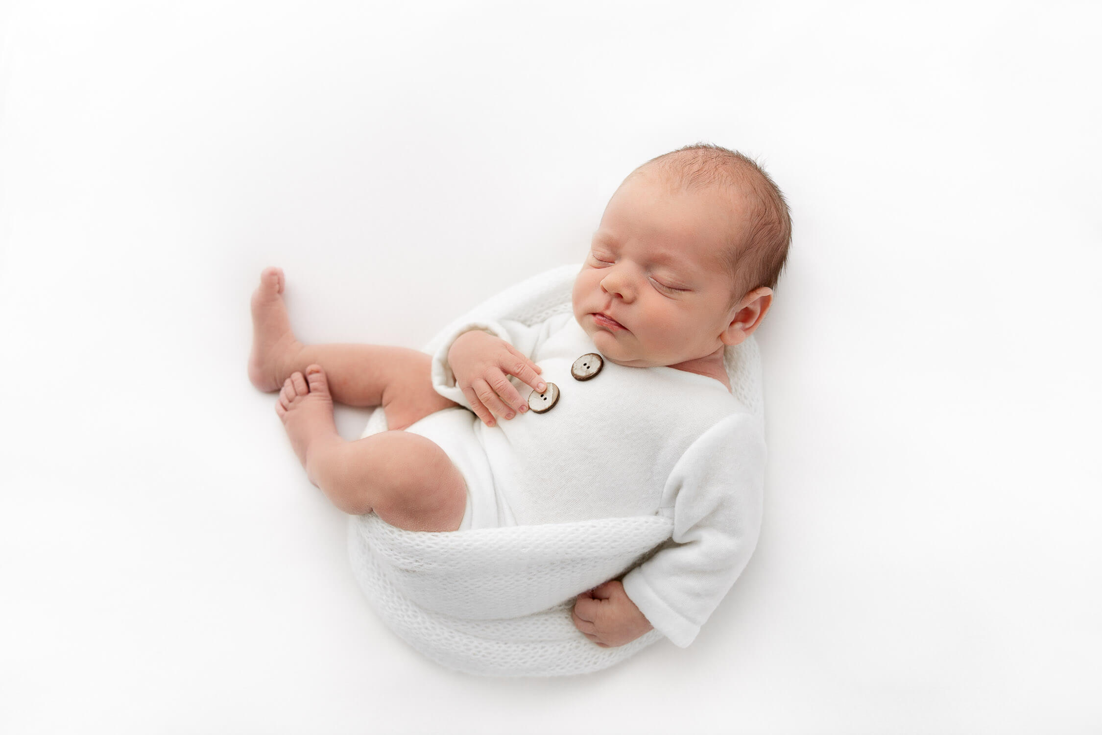 overhead image of baby boy wearing white romper sleeping on white fabric